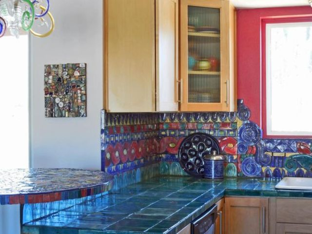 very bold teal tiles on the countertops and red and blue tiles on the backsplash