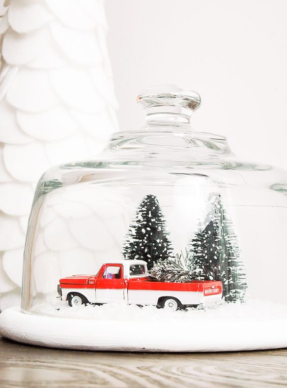 vintage snow globe with a pick up and tiny trees