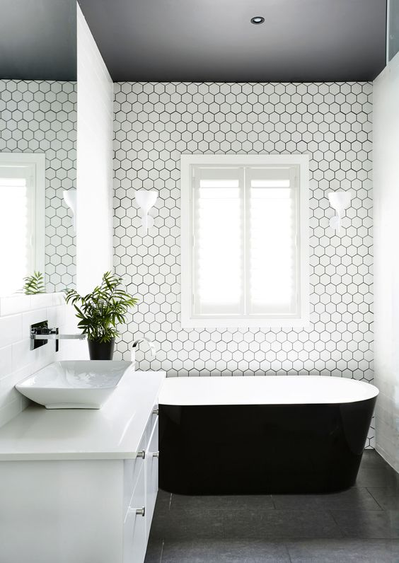 dark grey floors, a dark ceiling and white hex tiles with black grout to tie everything up