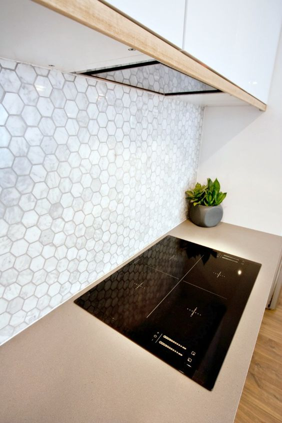 neutral mother of pearl hex tile backsplash for a modern kitchen