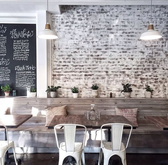 whitewashed brick walls, rough wood tables and metal chairs