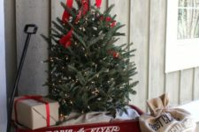 28 tiny faux tree with lights and a red bow in a trolley