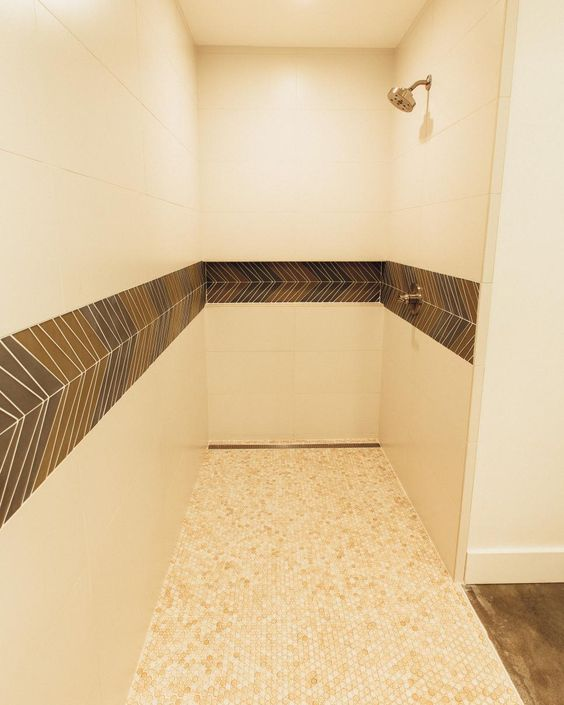 extra-large, cream-colored tiles cover the walls, and small, neutral tiles cover the floors