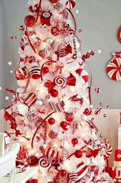 white tree with red ornaments and candy swirls