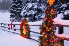 33 fence decorated with a lit up wreath and a Christmas tree on it