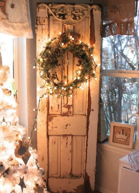 shabby chic door inside the house with a lit up wreath of greenery