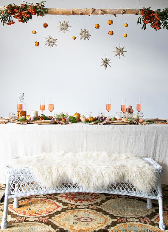 a wooden branch with glitter stars and pomanders, fur bench covers