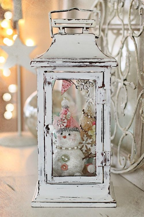 whitewashed lantern with a tiny bottle brush tree and a snowman inside