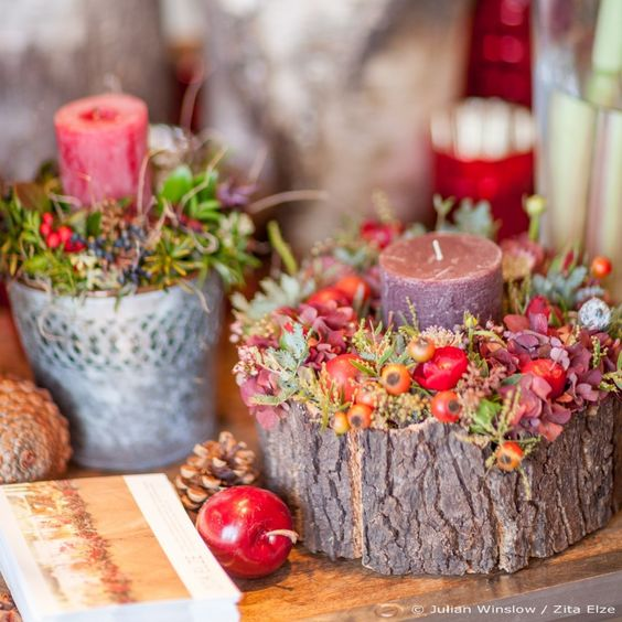 wooden log with a candle, flowers and berries