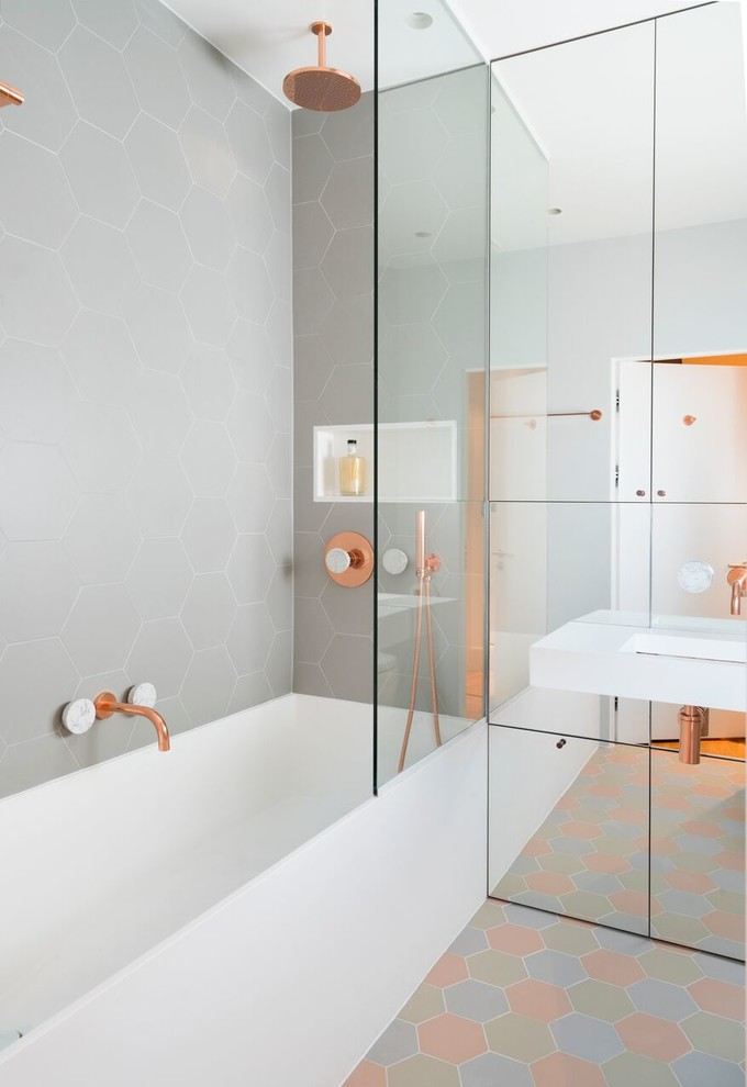 Pastel tones of floor tiles mixed with copper fittings makes this bathroom quite unique. Mirrored panelled cabinets not only provide storage space but also visually enlarge the space. (Amberth)