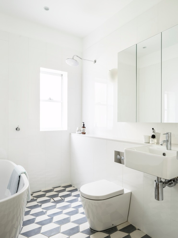 interesting half white half black hex tiles create interesting pattern in otherwise pure white bathroom (Decus Interiors)