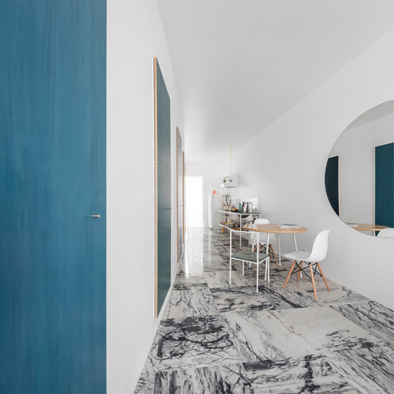 Black and wwhite marble floors and blue art works create a perfect contrast and a modern feel