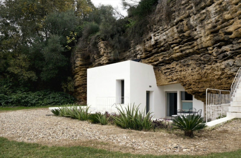 White plaster house architecture looks spotless next to discolored rock and there's a lot of greenery around
