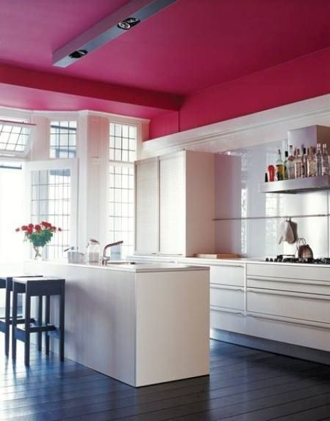 a fuchsia ceiling in this pure white kitchen looks very eye-catching and girlish