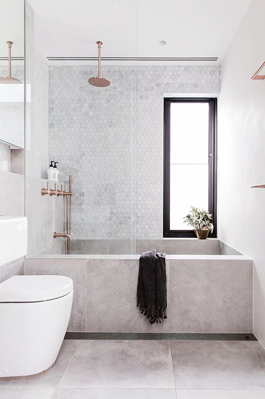 rectangular concrete bathtub looks great with marble tiles