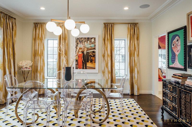 The dining space strikes with unique artworks and a horn legged dining table with a glass top