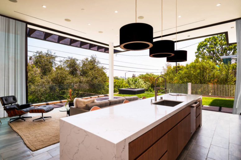 The kitchen is decorated in light-colored warm wood, marble surfaces and can be partly opened to outdoors
