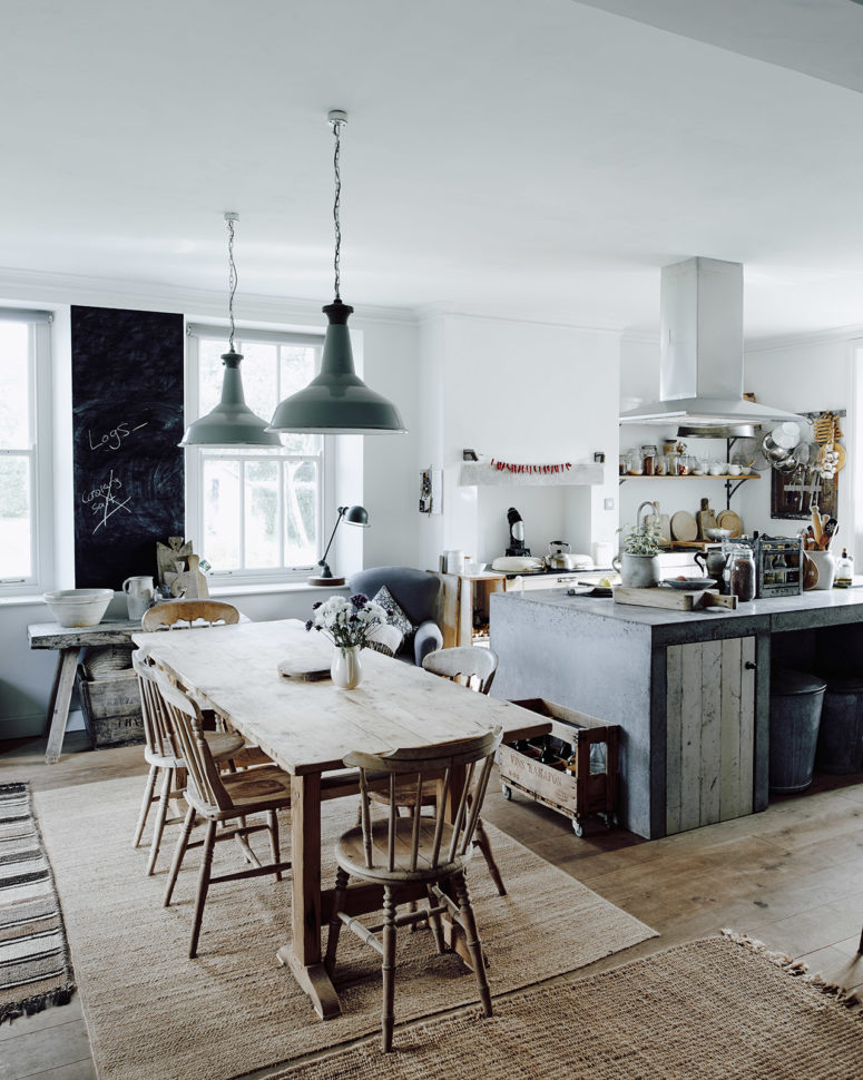 The kitchen is filled with light, the working surfaces are metal and concrete,  the furniture is wooden