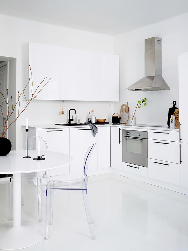 The kitchen is modern and laconic, with black handles that create a graphic feature and a lucite chair