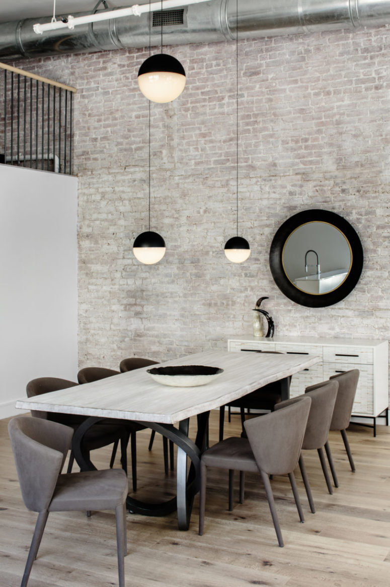 The whole space features an amazing whitewashed brick wall, and there's a whitewashed wooden dining table that echoes