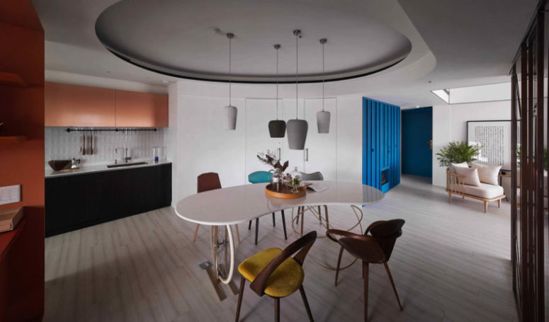 In the center of the apartment there's a dining zone accentuated with a ceiling and pendant lamps