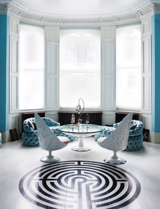 Matching blue chairs are placed by the large windows and there's a cool geo pattern on the living room's floor