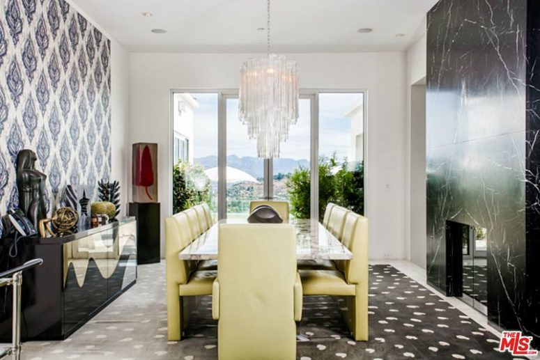 The dining area in black and white boasts of sunny yellow dining set and a glam chandelier