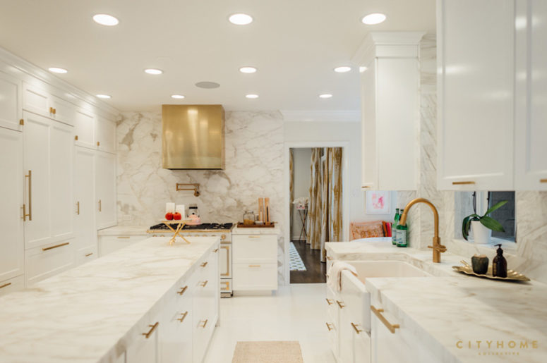The kitchen is totally clad with marble and spruced up with shiny brass touches and lots of lights