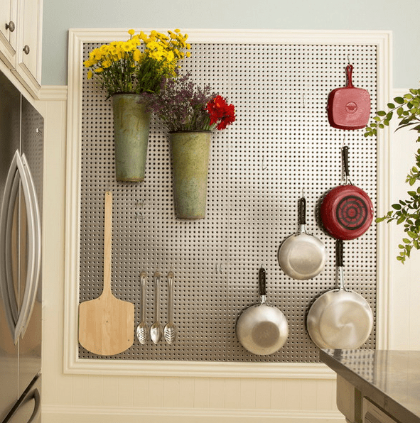 framed metal pegboard with hooks for utensils and metal pots attached