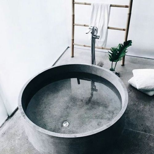 round concrete bathtub has a luxury feel
