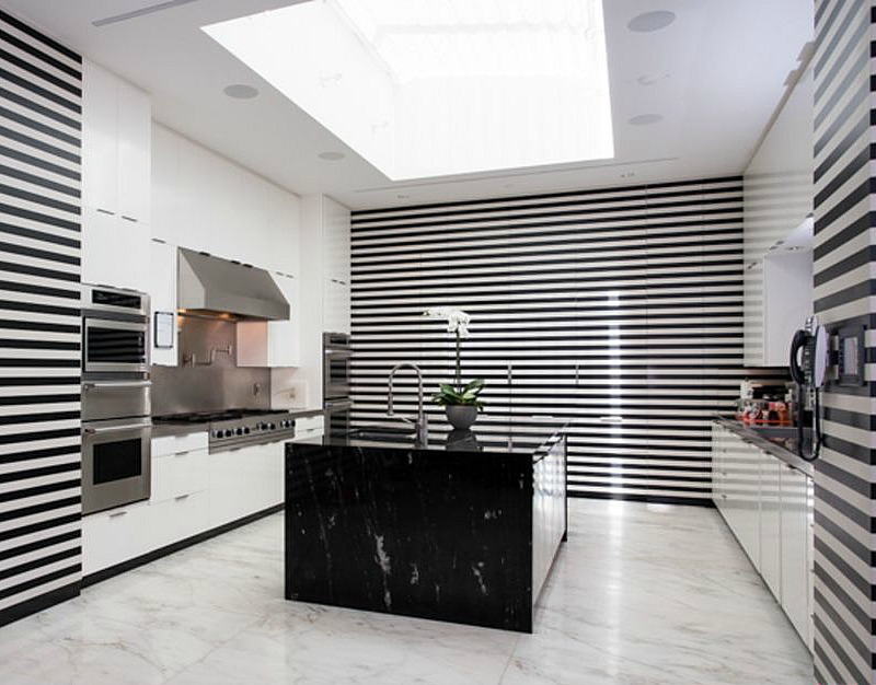 The kitchen is done in black and white stripes, with white drawers and a black marble kitchen island