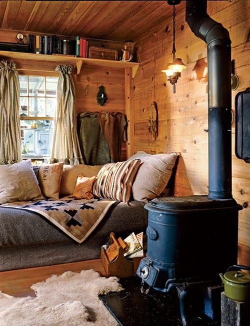 a sofa by the window with pillows and blankets