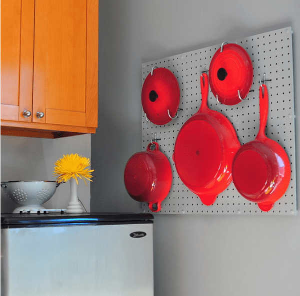 metal pegboard with hot red pans and frying pans looks like a decoration