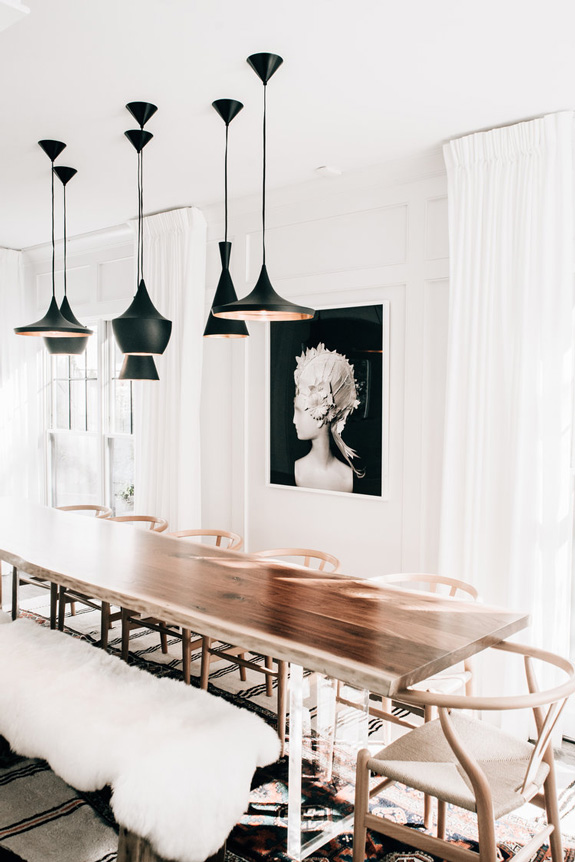 A composition of hanging black lamps and a dark artwork accentuate the subtle shade space