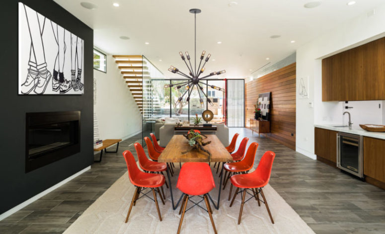 The dining room is decorated with red chairs, cool wall art and a statement chandelier