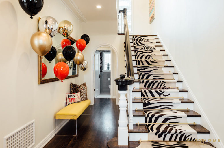 The entryway surprises with a bold yellow bench, balloons and a zebra print rug