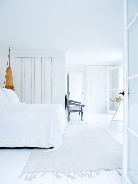 The relaxed all-white master bedroom makes you feel already on the beach, and I love the shabby blue seat