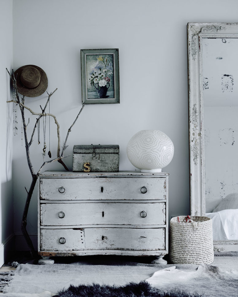 The bedroom is shabby and whitewashed, with a sideboard and an oversized mirror, textiles and crochets