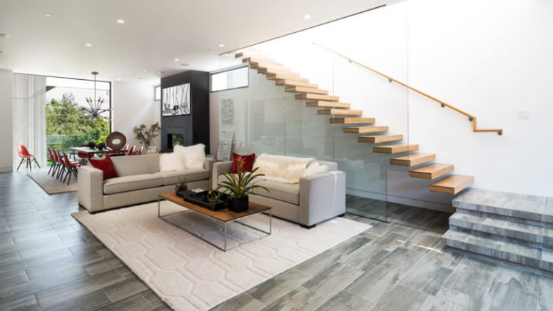 The floors are covered with grey and beige tiles, and the staircase is exciting, of wood and glass, looks very modern