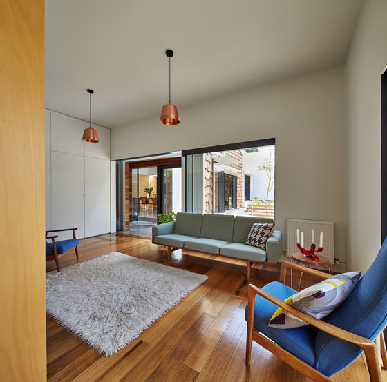 The living room has mid-century modenr features, it's rather cozy and filled with light