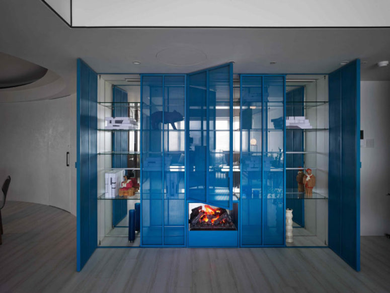 There's a bold blue sheer storage unit with a built in fireplace, such an interesting solution