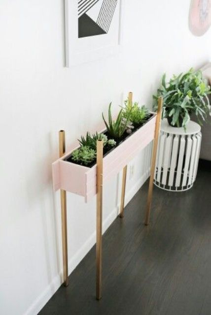such a stylish blush planter on metallic legs can accentuate the room