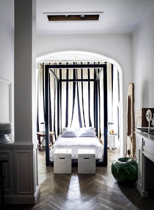 The bedroom is full of light, there's a large frame bed placed under an arched ceiling