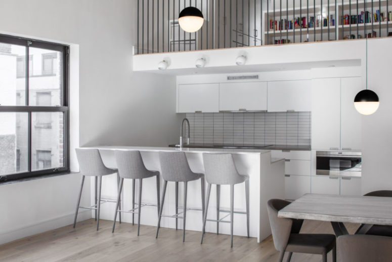 The kitchen is small and neutral, done in white and light grey, with a kitchen island as a breakfast nook