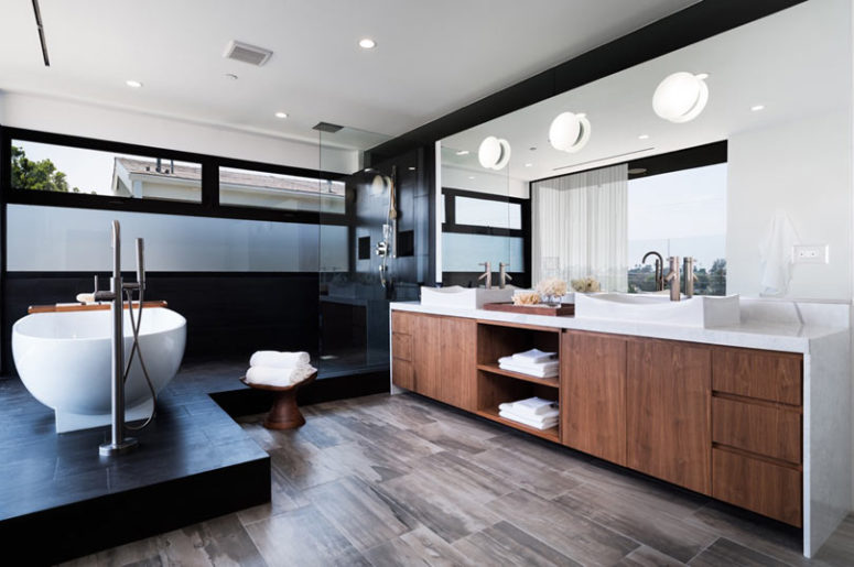 The master bathroom is done in warm woods and black tiles, looks very chic and laconic