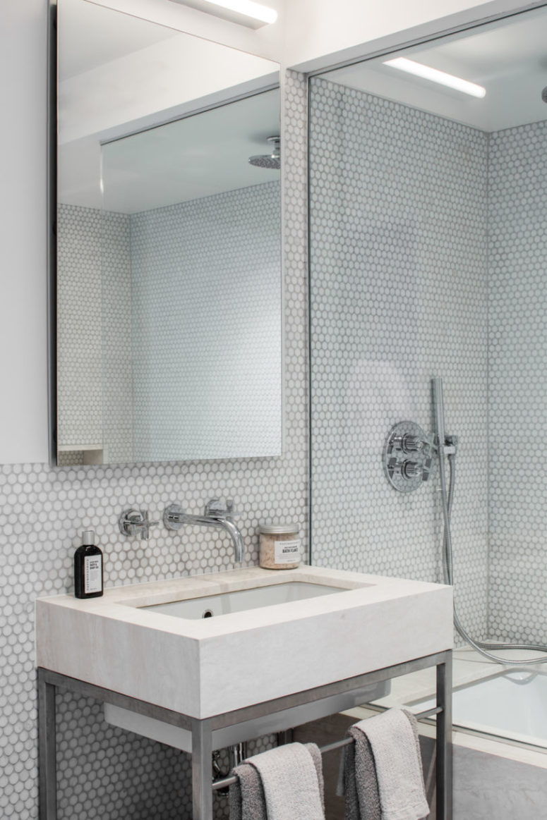 The bathroom is a large modern one, with white penny tiles, nickel faucets and some concrete