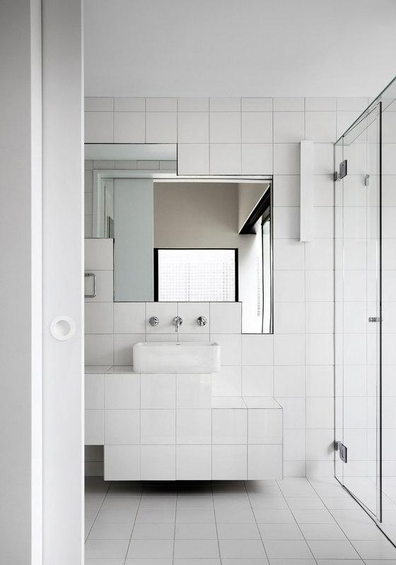 The bathroom is modern and chic, I love the geometry of mirrors here, they create a simple yet eye catching accent