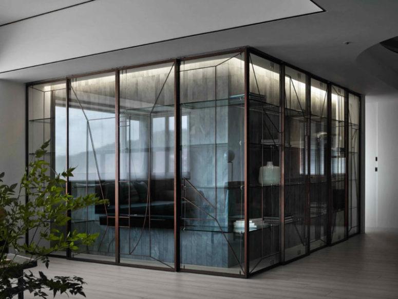 The glass cabinet with a TV unit has a unique geometric design
