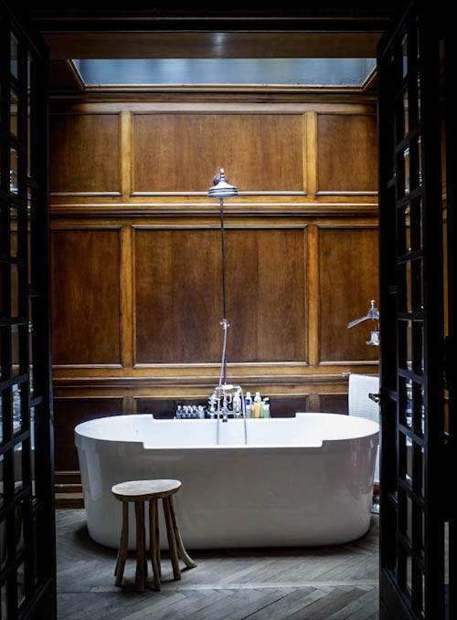 The bathroom looks breathtaking - only oak panels, ash grey wooden floors and a free-standing bathtub