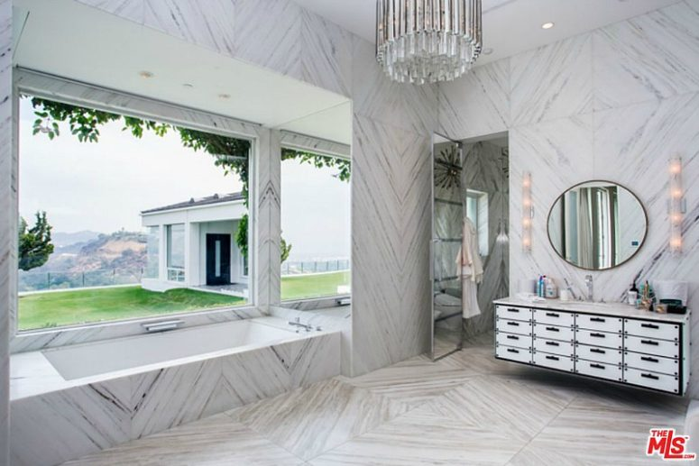 The master bathroom is clad with light-colored marble, the design is totally glam